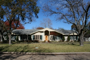 This is a photo of a ranch style house with pecan trees, bay windows and two columns flanking the wooden front door.