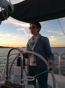 This is a photo of the author at the wheel of a 30-foot sailboat on a lake.
