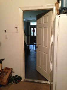 This is a picture of an open door leading into a house.