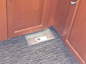 This is a photo of a box holding rat bait under a gym locker